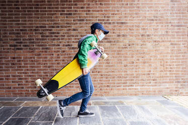 Boy wearing protective mask and walking with longboard in front of a brick wall - JCMF00682
