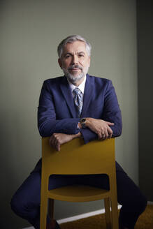 Portrait of confident mature businessman sitting on a chair - RBF07649