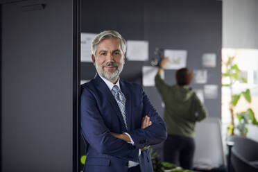 Portrait of confident mature businessman in office with woman in background - RBF07670