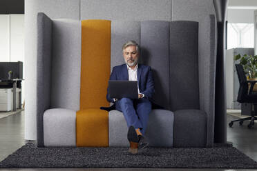 Mature businessman sitting on couch in office using laptop - RBF07679