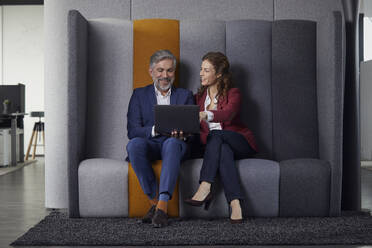 Businesswoman and businessman sitting on couch in office sharing laptop - RBF07682