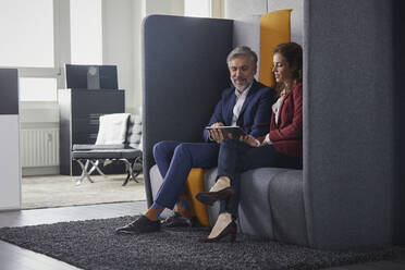 Businesswoman and businessman sitting on couch in office sharing laptop - RBF07685