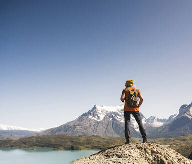 Hiker in mountainscape at Lago Pehoe in Torres del Paine National Park, Patagonia, Chile - UUF20236