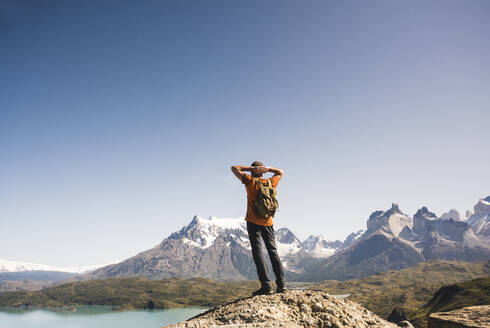 Hiker in mountainscape at Lago Pehoe in Torres del Paine National Park, Patagonia, Chile - UUF20239