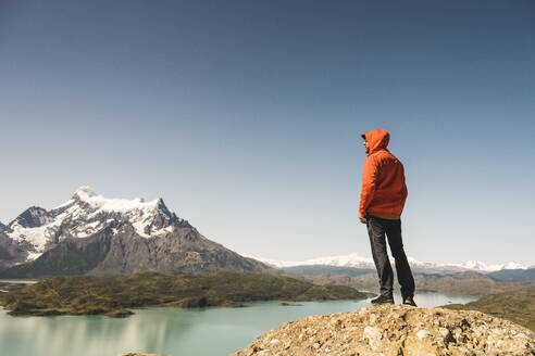 Hiker in mountainscape at Lago Pehoe in Torres del Paine National Park, Patagonia, Chile - UUF20242