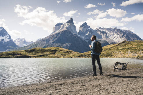 Hiker in mountainscape at lakeside in Torres del Paine National Park, Patagonia, Chile - UUF20245