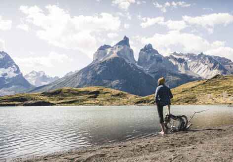 Hiker in mountainscape at lakeside in Torres del Paine National Park, Patagonia, Chile - UUF20251