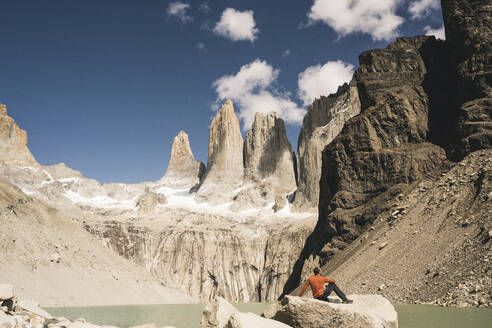 Hiker resting in mountainscape at lakeside at Mirador Las Torres in Torres del Paine National Park, Patagonia, Chile - UUF20269