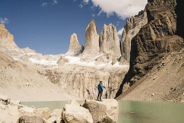 Hiker in mountainscape at lakeside at Mirador Las Torres in Torres del Paine National Park, Patagonia, Chile - UUF20272
