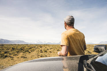 Rear view of man at car in remote landscape in Patagonia, Argentina - UUF20275