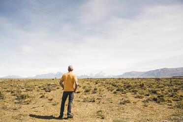 Rear view of man standing in remote landscape in Patagonia, Argentina - UUF20281