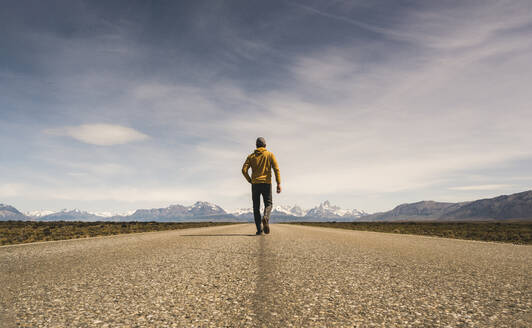 Man walking on a road in remote landscape in Patagonia, Argentina - UUF20284