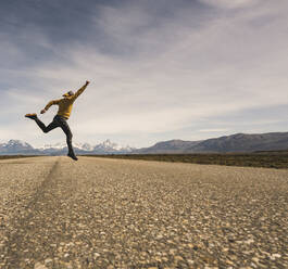 Man jumping on a road in remote landscape in Patagonia, Argentina - UUF20287