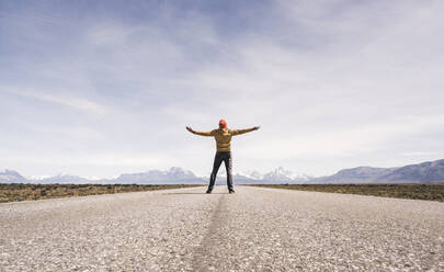 Man with outstretched arms standing on a road in remote landscape in Patagonia, Argentina - UUF20290