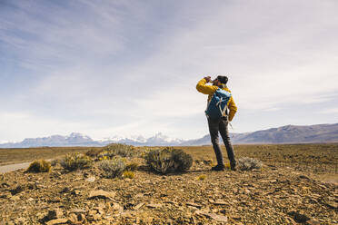 Hiker drinking from bottle in remote landscape in Patagonia, Argentina - UUF20296