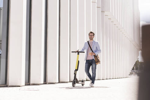 Young man with e-scooter and takeaway drink in the city, Lisbon, Portugal - UUF20316