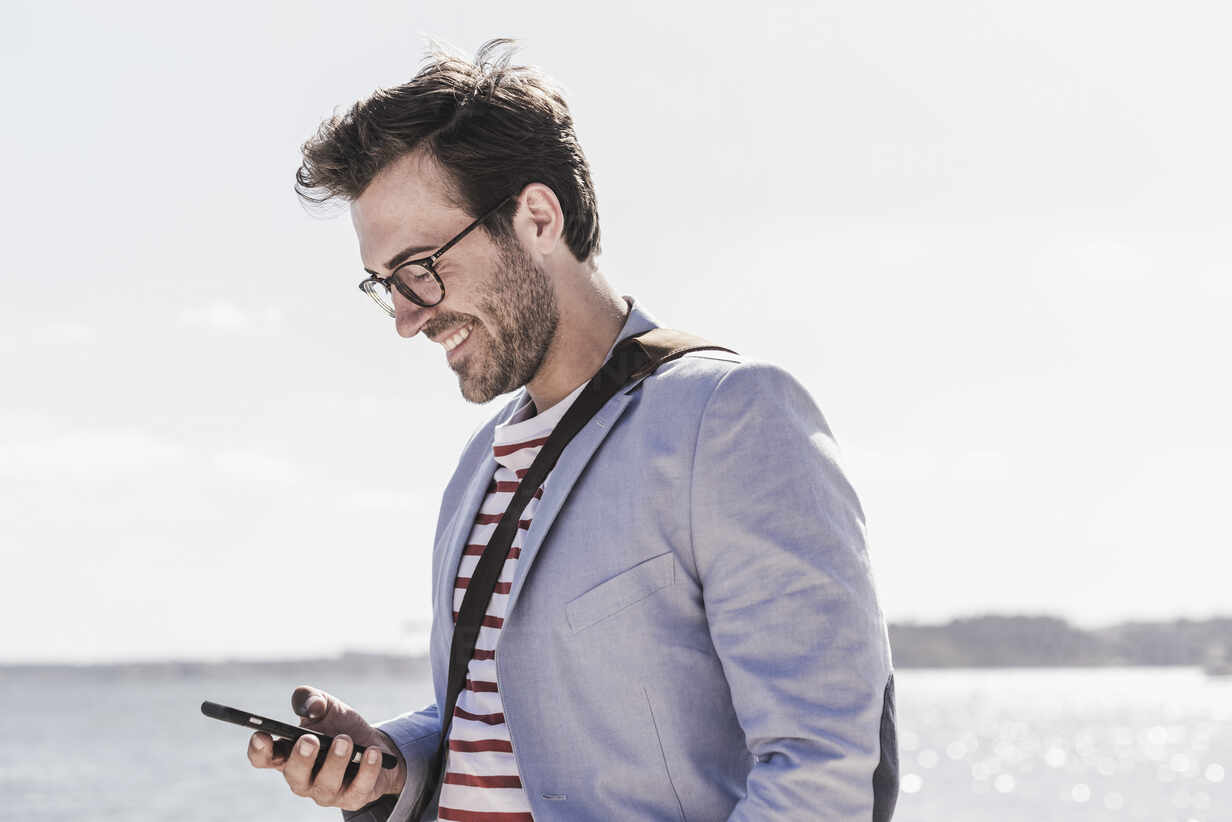 Smiling young man using smartphone on the waterfront - UUF20340 - Uwe Umstätter/Westend61