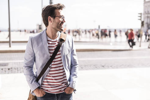 Smiling young man in the city looking sideways, Lisbon, Portugal - UUF20349