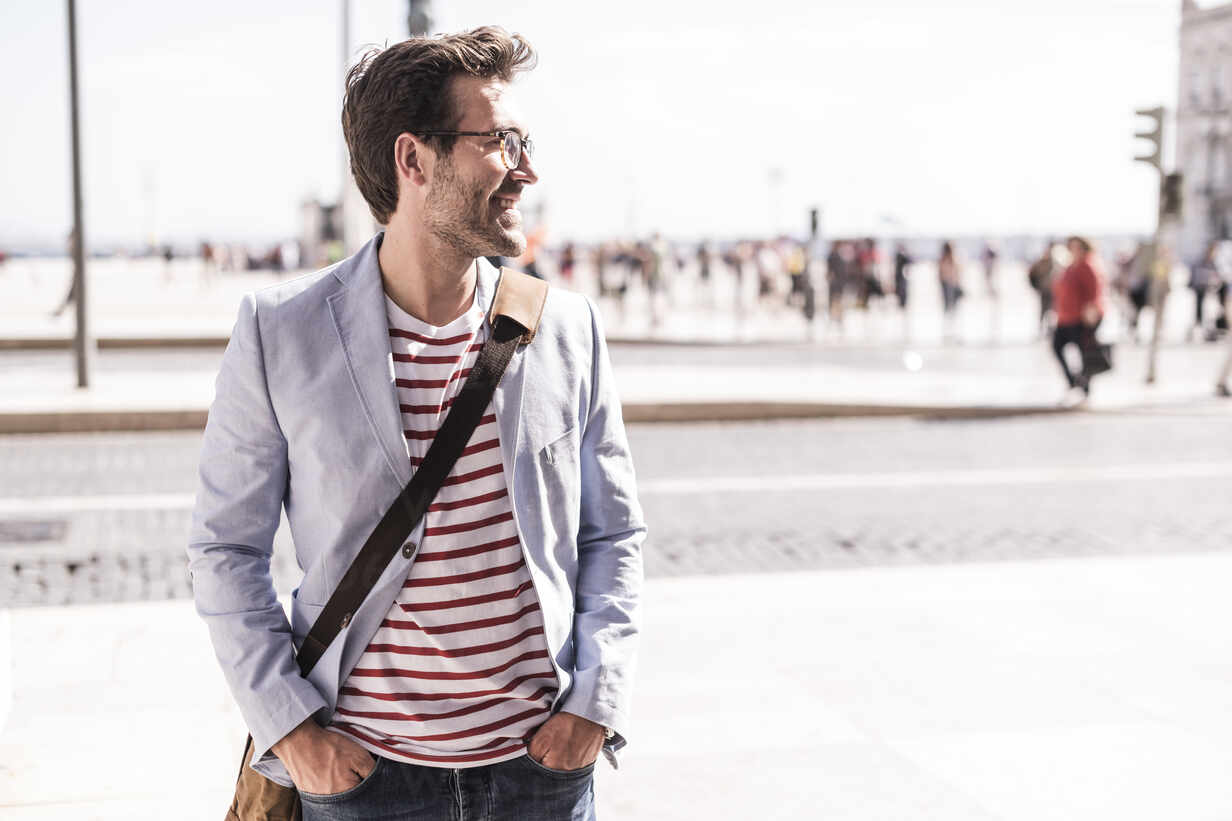 Smiling young man in the city looking sideways, Lisbon, Portugal - UUF20349 - Uwe Umstätter/Westend61