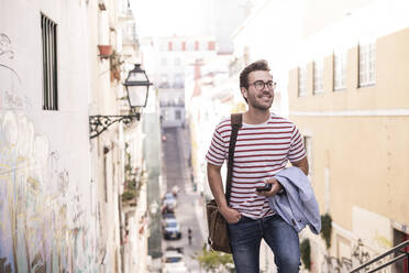 Young man walking in the city, Lisbon, Portugal - UUF20352