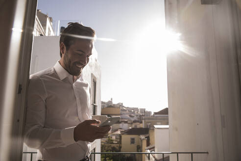 Young man with cell phone and coffee cup on a balcony - UUF20355