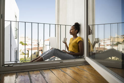 Young woman sitting on a balcony with laptop and coffee cup - UUF20361