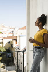 Young woman with coffee cup on a balcony - UUF20364