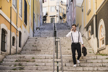 Smiling young man on the phone walking down stairs in the old town, Lisbon, Portugal - UUF20367
