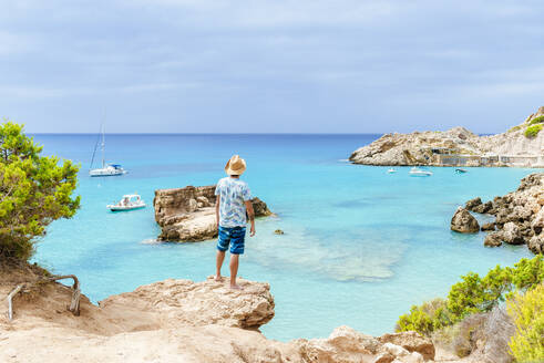 Man standing on cliff looking at sea, Ibiza, Spain - KIJF02998