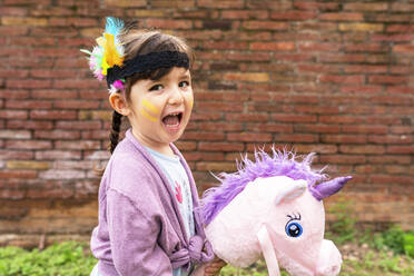 Portrait of girl with braids and feather headdress riding a pink unicorn - GEMF03640
