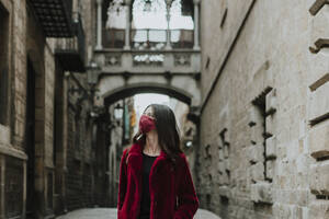 Woman wearing face mask looking away while standing on empty alley of Gothic Quarter during quarantine, Barcelona, Spain - GMLF00177
