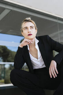 Portrait of young businesswoman wearing black pantsuit looking at distance - TCEF00575