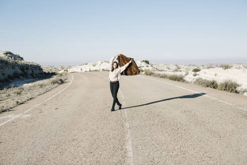Full length of smiling woman holding jacket while walking on road at desert against clear sky - XLGF00126
