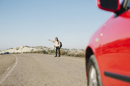 Full length of woman hitchhiking on roadside at desert against clear blue sky - XLGF00129