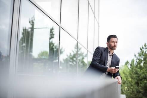 Thoughtful businessman leaning on railing while looking away from office balcony - DIGF10269