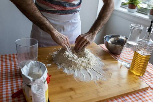 Crop view of man in kitchen preparing dough - WPEF02878
