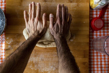 Man's hands kneading dough, top view - WPEF02887