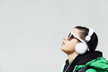 Boy wearing sunglasses listening music with headphones - JCMF00698