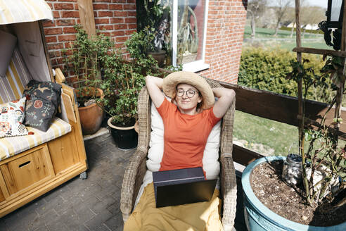 Portrait of mature woman with laptop relaxing on terrace - KMKF01313