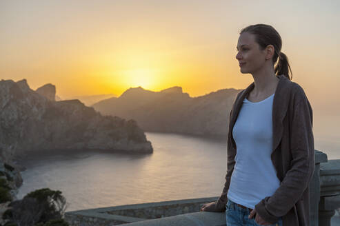 Relaxed woman enjoying sunset at Cap Formentor, Mallorca, Spain - DIGF10355
