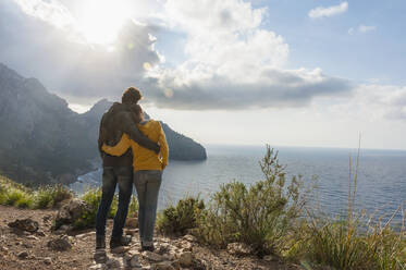 Back view of couple standing arm in arm looking to the sea, Mallorca, Spain - DIGF10358