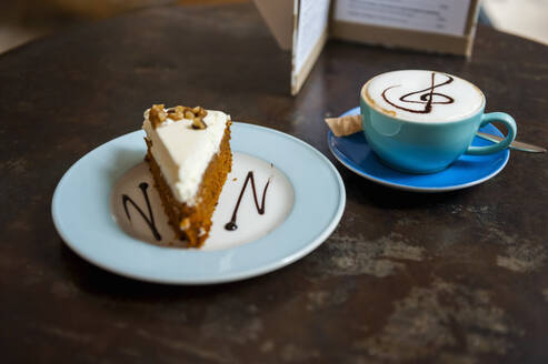 Cup of Cappuchino and piece of cake on table in a coffee shop - DIGF10370