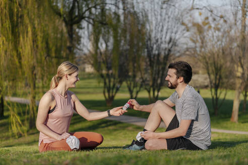 Smiling man giving hand sanitizer to woman while sitting on grass at park - STDF00226