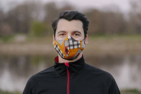 Portrait of confident young man wearing face mask at park during coronavirus - STDF00244