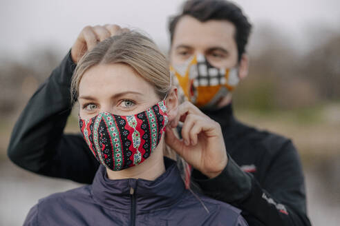 Portrait of young woman while man adjusting face mask for her at park - STDF00247