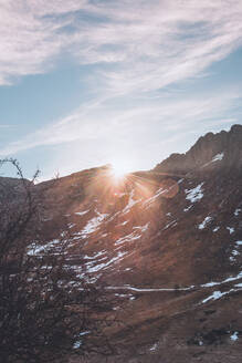 Idyllic shot of sunbeam on mountain peak against sky during sunrise - FVS00226