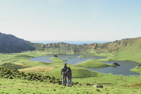 Rear view of couple looking at lake and mountains against clear sky on sunny day, Corvo, Azores, Portugal - FVSF00235