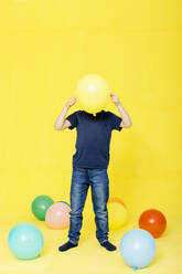 Boy holding yellow balloon in front of face while standing against colored background - JRFF04421