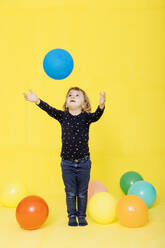 Cute girl catching balloon while standing against yellow background - JRFF04424