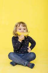 Full length of preschool girl holding banana while sitting with cross-legged and looking away against colored background - JRFF04427